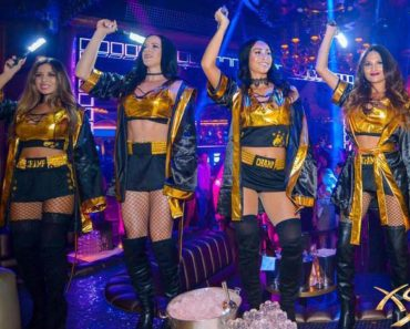 Cocktail servers dressed up in fight gear holding lights and standing on tables.