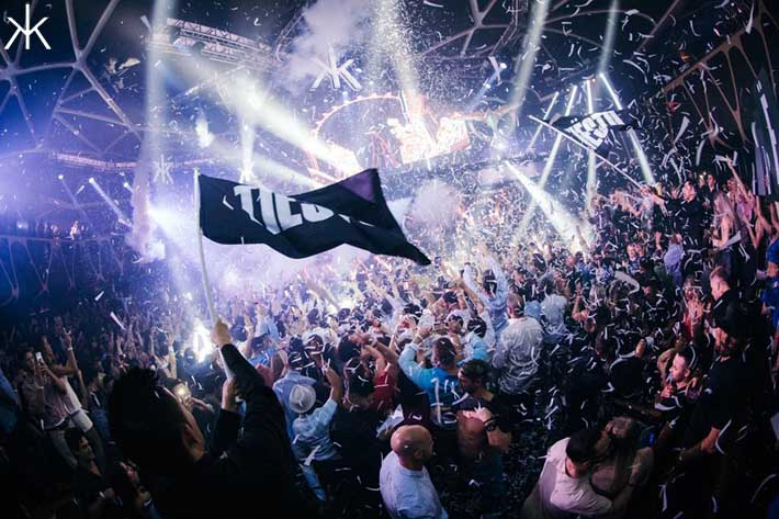 A tiesto flag is waived above the crowd as confetti falls down.