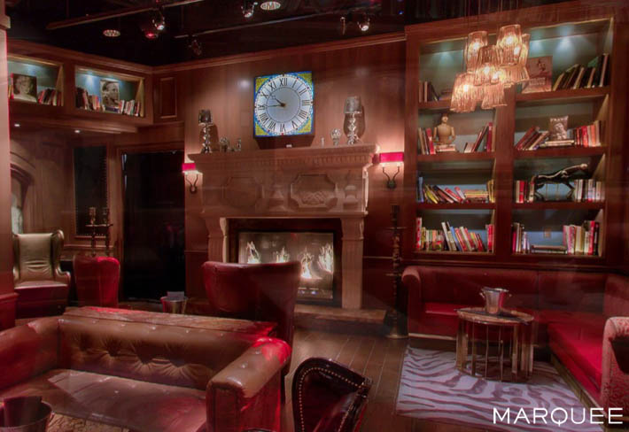 A fireplace, bookcase, and pool table inside The Library at Marquee Las Vegas