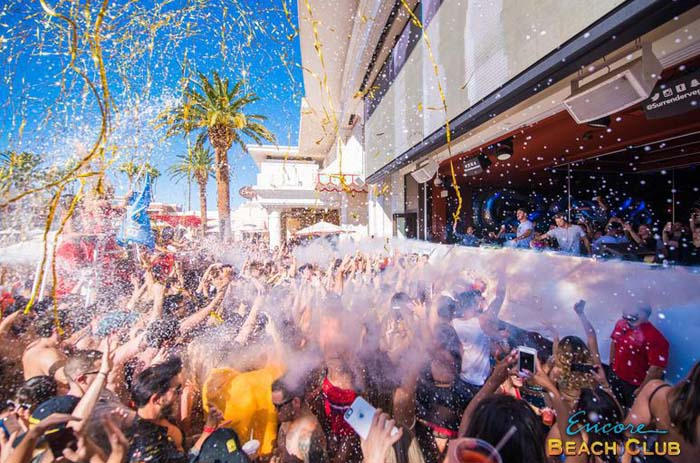 A photo of the pool party at Encore Beach Club featuring streamers and smoke machines