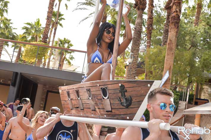 A Rehab Beach Club bottle presentation featuring a waitress carrying a bottle on a boat