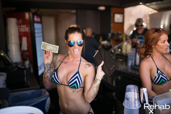 A waitress with tattoos sticks out her tongue for the camera at Rehab's Grotto Bar