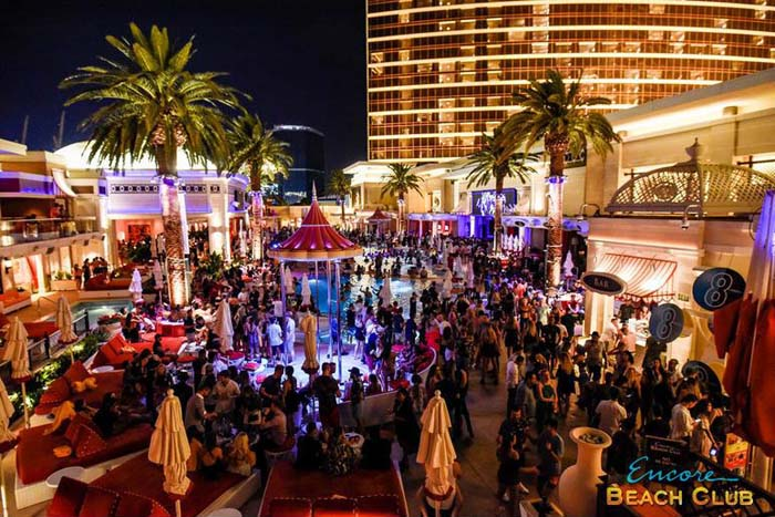 EBC lights up the night with its nighttime pool party. Palm trees, cabanas, daybeds, and the beautiful Encore hotel is in the background.