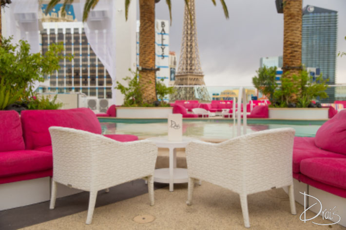 A photo showing the poolside banquette table option featuring two chairs, sofa and a small table overlooking the Drai's pool.