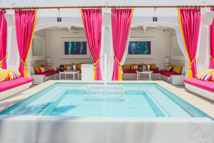A look inside the bungalows at Drai's Nightclub featuring a private pool, couches, and a flat-screen TV.