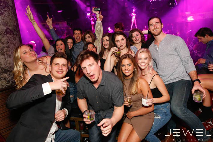 A group of girls and guys wearing various clothing options at Jewel Nightclub including dresses, skirts, jeans and collared shirts.