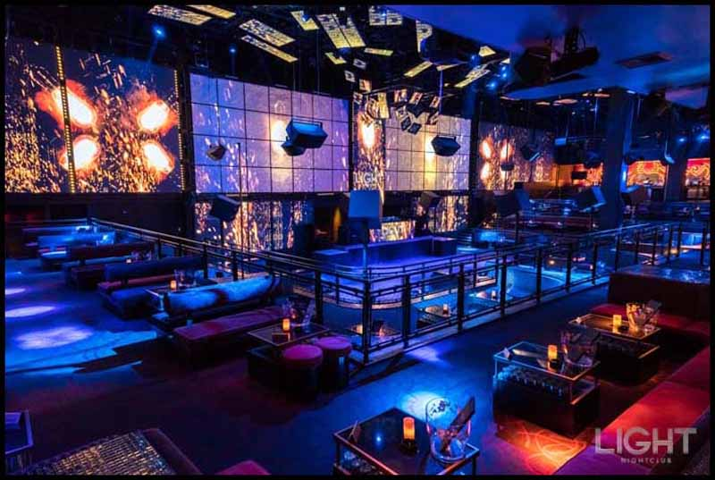 A photo of Light Nightclub's main room showing the bottle service tables and LED screens.
