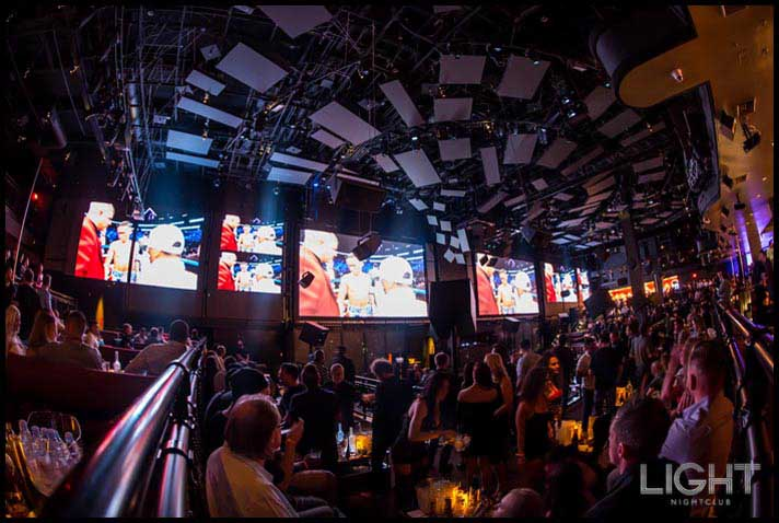 Groups of people watching a UFC match on Light's LED screens.