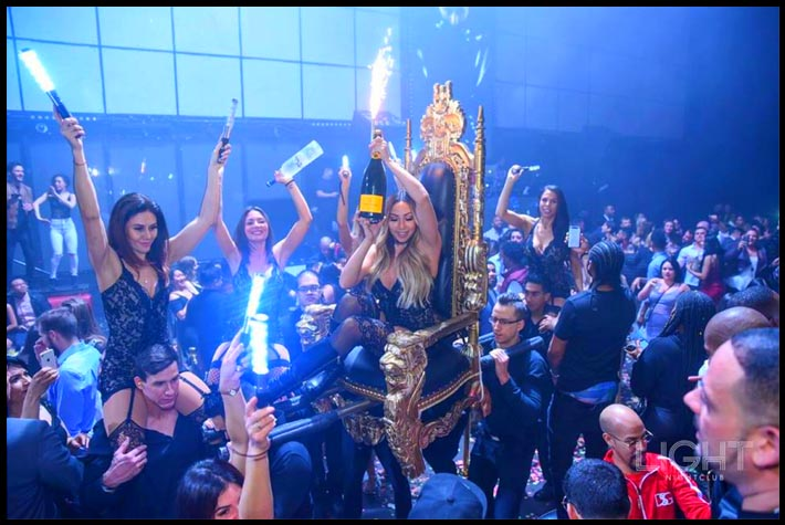A cocktail server carrying a bottle with sparklers is carried on a throne.