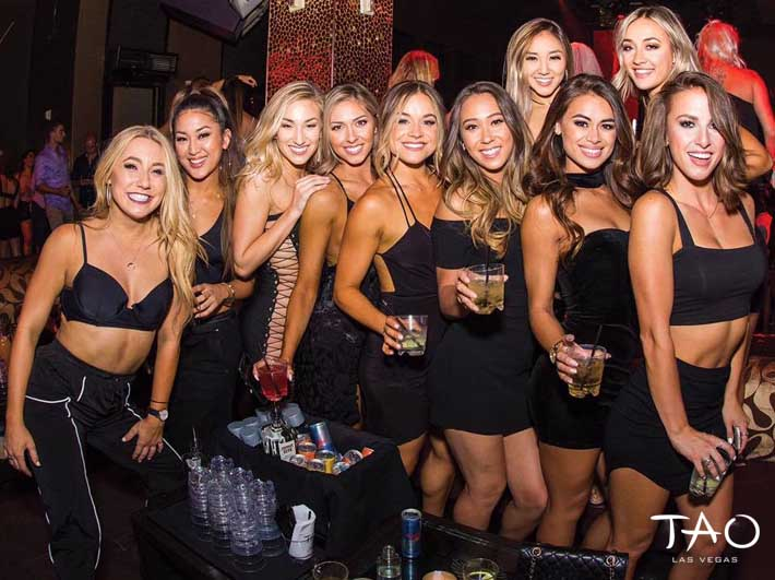 Ladies dressed in black dresses holding drinks at a TAO bottle service dance floor table