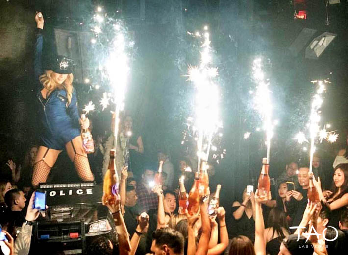 A cocktail waitress dressed in a police uniform is carried across the club on a police car. Sparklers shoot off the top of the bottles.