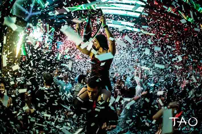 Confetti surrounds a waitress carrying a bottle to a table.